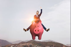 Make your savings work for you . Mixed media. Young cheerful businesswoman flying on pink piggy bank. Mixed media Stock Image