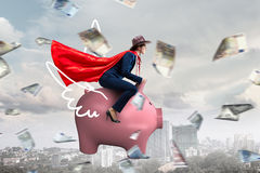 Make your savings work for you . Mixed media. Young cheerful businesswoman flying on pink piggy bank. Mixed media Royalty Free Stock Photos