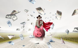 Make your savings work for you. Young businesswoman riding on piggy bank presenting banking and saving concept Royalty Free Stock Photography