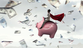 Make your savings work for you. Young businesswoman riding on piggy bank presenting banking and saving concept Royalty Free Stock Photos