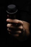 Make yourself heard. A hand holding a microphone Royalty Free Stock Photos