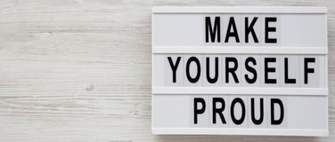 `Make yourself proud` words on a modern board on a white wooden background, top view. Flat lay, overhead, from above. Copy space royalty free stock photos