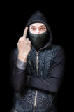 Maked rude criminal or bandit showing middle finger. Low key isolated on black Stock Photo