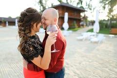 Makedans med frun som håller exponeringsglas av vin på trädgård royaltyfri bild