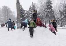 Makeevka,乌克兰- 2016年1月07日:Makeevka,乌克兰- 2016年1月07日:使用在一个中心广场的多雪的小山的孩子 免版税图库摄影