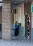 Makeevka, Ucrânia - 30 de julho de 2015: Mulher idosa perto de um ATM foto de stock royalty free