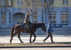 Makeevka, Ucrania - febrero, 22, 2015: Paseo del muchacho una república popular de Donetsk del loshadisoldata durante el día de f Imagen de archivo