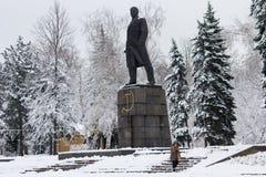 Makeevka Ukraina - November 22, 2017: Kvinnan i en apelsinwaistcoat gör ren snön nära monumentet till den kommunistiska ledaren L royaltyfri bild