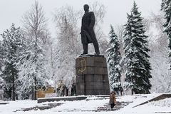 Makeevka, Ukraine - November 22, 2017: Woman in an orange waistcoat cleans the snow near the monument to the communist leader Leni. N in a snow-capped city Royalty Free Stock Image