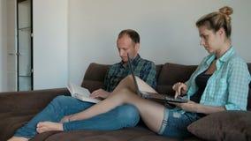 Makefrusammanträde på soffan i vardagsrum vilar i aftonen som gör stock video