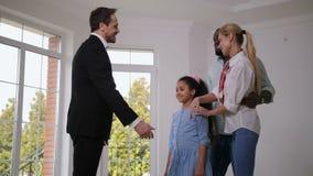 Makelaar die huissleutels geven aan gelukkig weinig huiseigenaar stock videobeelden