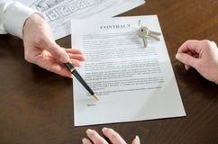Makelaar in onroerend goed die de handtekeningsplaats van een contract tonen Stock Foto's
