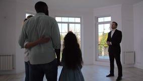 Makelaar in onroerend goed die familieruimte binnenshuis tonen stock videobeelden