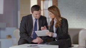 Makelaar in onroerend goed die foto's op tablet tonen aan zakenmancliënt stock videobeelden