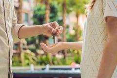 Makelaar in onroerend goed die sleutels geven aan flateigenaar, die verkopende bezitszaken kopen Sluit omhoog van mannelijke hand stock fotografie