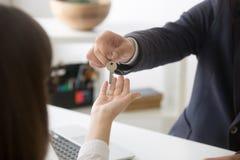 Makelaar in onroerend goed die sleutels geven aan nieuwe huis vrouwelijke koper royalty-vrije stock afbeelding