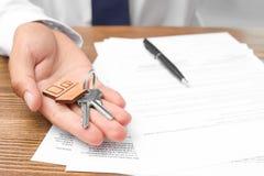 Makelaar in onroerend goed met sleutels en documenten stock afbeelding