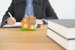 makelaar in onroerend goedmakelaar in onroerend goed het schrijven nota met huismodel buying stock afbeeldingen