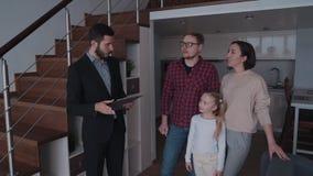 Makelaar in onroerend goedmens die nieuw huis tonen aan gelukkige familie van drie mensen stock video
