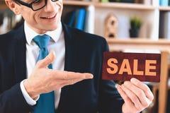 Makelaar in onroerend goedzitting bij bureau in bureau De makelaar in onroerend goed stelt verkoopteken voor stock foto