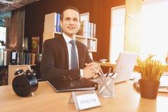 Makelaar in onroerend goedzitting bij bureau in bureau De mens stelt op camera stock fotografie