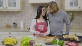 Maken äter ett stycke av tomaten, medan hans fru klippte grönsaken för sallad arkivfilmer