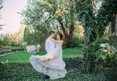 Maken cirklar hans favorit- kvinna i armarna Den rödhåriga flickan i ett blygsamt, grå färg klär i lantlig stil stilfullt arkivfoton