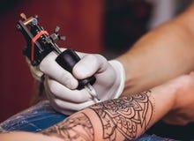 Maken de tatoegerings hoofd beschermende handschoenen een tatoegering in zwarte inkt op de hand van het meisje Royalty-vrije Stock Foto