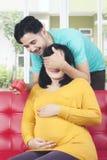 Maken förvånar den gravida frun med gåvan royaltyfri bild