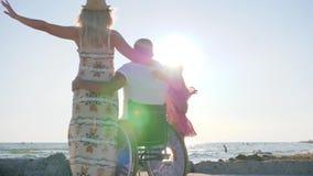 Maken i frun för kramen för hjulstol och lilla flickan i panelljus, familj kramar sig, den rörelsehindrade mannen med frun och do stock video