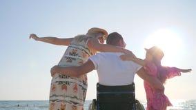 Maken i rullstolkramfru och liten flicka i panelljus, inaktiverade kramar hans fru och dotter som var ogiltiga stock video