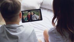 Maken och frun talar till den videopd appellen vänför online-danande via minnestavlan, gladlynta kvinnor på skärmen visar stock video