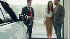 Maken och frun väljer deras första bil tillsammans och talar till den säkra affärsbiträdet i motorisk show, lycklig kvinna stock video