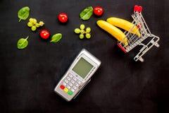 Makend aankoop met bankmachine, minikarretje en producten op zwarte bureau hoogste mening als achtergrond online stock afbeelding