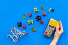 Makend aankoop met kaartmachine, betaalpas, minikarretje en producten op blauwe bureau hoogste mening als achtergrond online royalty-vrije stock fotografie