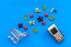 Makend aankoop met kaartmachine, minikarretje en producten op blauwe bureau hoogste mening als achtergrond online stock afbeeldingen