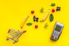 Makend aankoop met kaartmachine, minikarretje en producten op gele bureau hoogste mening als achtergrond online stock fotografie