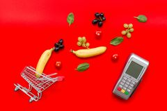 Makend aankoop met kaartmachine, minikarretje en producten op rode bureau hoogste mening als achtergrond online stock foto's