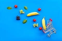 Makend aankoop met mini omhoog karretje en producten op blauwe bureau achtergrond hoogste meningsspot online stock afbeelding