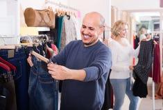 Maker som köper par av klassisk jeans i boutique Royaltyfria Foton