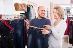 Maker som köper par av klassisk jeans i boutique Royaltyfri Foto