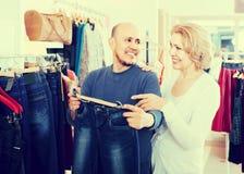 Maker som köper par av klassisk jeans i boutique Arkivbilder