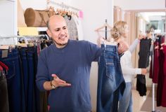 Maker som köper par av klassisk jeans i boutique Royaltyfria Bilder