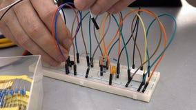 Maker, student of elektronikaingenieur die de kring van de prototypeelektronika op broodplank ontwikkelen stock footage