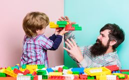 He makes it fly. small boy with dad playing together. father and son play game. Dream about fly. love. child development. Happy family leisure. building plane stock photography