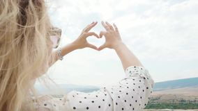 Makes a heart shape out of her fingers, a young attractive woman with blond hair in casual clothes on vacation, love of. Nature and the world, a lady in dark stock footage