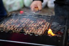 Makes shish kebab from fresh meat. Fries large juicy pieces of meat on the grill. Makes shish kebab from fresh meat. Fries large juicy pieces of meat on the royalty free stock photography