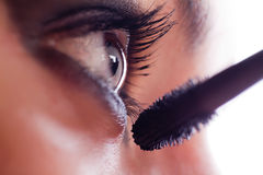 She makes-up eyelashes with mascara a special wand Stock Image