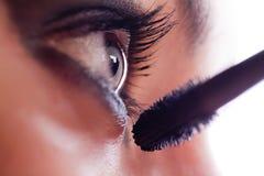She makes-up eyelashes with mascara a special wand. Closeup macro shot of female eye girl applying massacra on eyelashes stock image