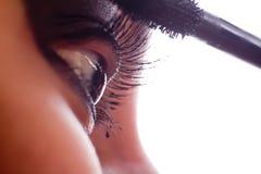 She makes-up eyelashes with mascara a special wand. Closeup macro shot of female eye girl applying massacra on eyelashes stock photography